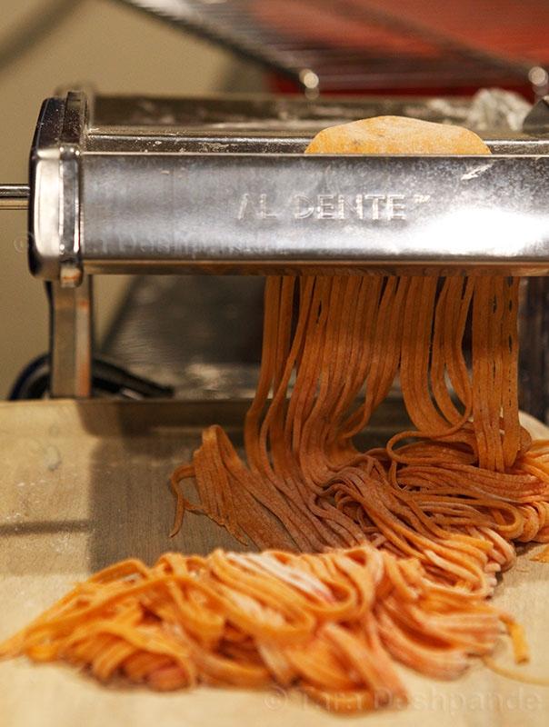 Slicing the carrot and beetroot pasta sheets through my machine   Photo by Binaifer Barucha